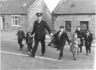 "Crossing the road to go to School with the local ""Bobby"" It probably dates from 1967."